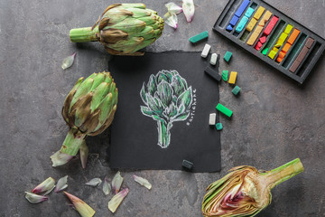 Tasty raw artichokes with picture on grey table