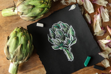 Tasty raw artichokes with picture on wooden table