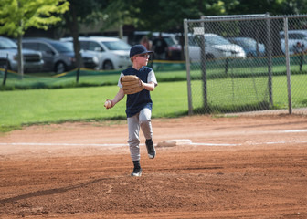 Full length Action photo of a Little League baseball pitcher throwing a pitch. Young boy with glasses focused on winning