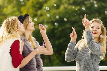 Women friends blowing soap bubbles.