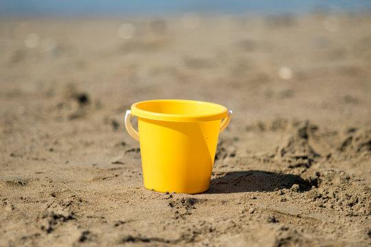 yellow plastic bucket on beach