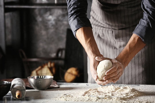 Young man preparing dough for bread in kitchen