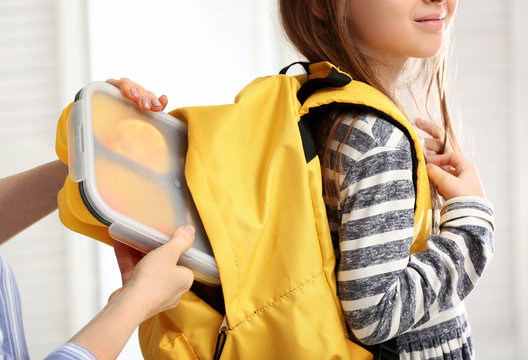 Mother packing lunch box into backpack of cute daughter at home