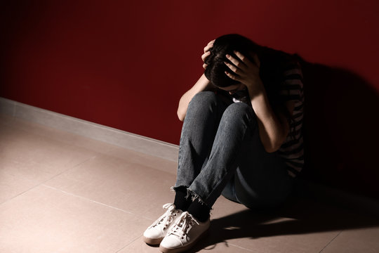 Young depressed woman thinking about suicide near wall