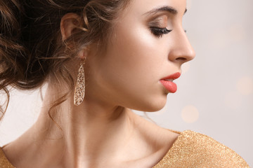 Young woman with beautiful jewelry against defocused lights, closeup