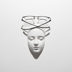 Styilish glasses with plaster mask face for reading, long crossing shadows on a white background, copy space. Top view.