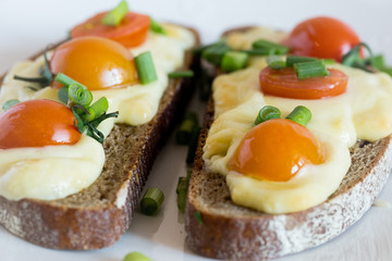 Multigrain toast bread with melt gouda or kaseri cheese and small tomatoes and green onion on top