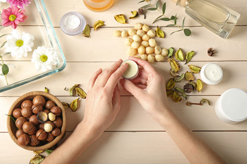 Female hands and cosmetics with extract of macadamia nuts on wooden background
