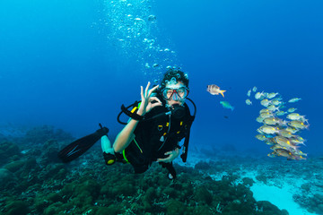 Young woman scuba diver showing OK gesture.
