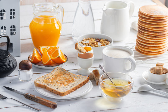 Healthy breakfast eating concept, various morning food - pancakes, soft-boiled egg, toast, oatmeal, granola, fruit, coffee, tea, orange juice, milk on white wooden table