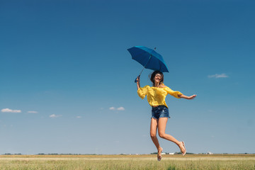 Beautiful Caucasian girl in yellow blouse and denim shorts jumping with blue umbrella outdoors. Blue sky with clouds in background.