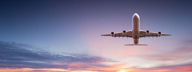 Tuinposter Vliegtuig Commercial airplane jetliner flying above dramatic clouds in beautiful sunset light. Travel concept.