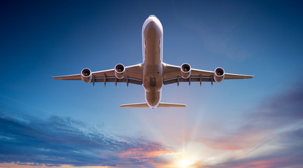 Commercial airplane jetliner flying above dramatic clouds in beautiful sunset light. Travel concept. Fotobehang