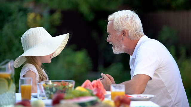 Girl telling exciting story to grandfather, spending time together, relationship