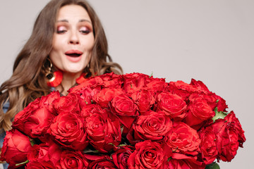 Studio portrait of shocked model with brunette hair and make up looking with astonishment at beautiful big bouquet of roses. Copyspace on white. Isolate. Studio shot.