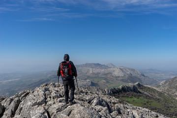 senderista en la cima de la montaña y frente al torcal de Antequera