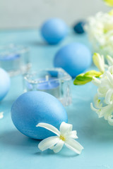 Easter eggs, candles and white hyacinth on a blue concrete