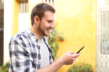 Profile of a man using smart phone outdoors