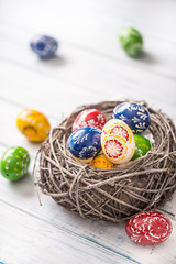Close-up multicolored easter eggs in basket on wooden table