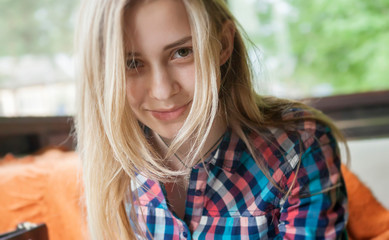 A girl with beautiful eyes, in a plaid shirt, sits in a summer cafe against the background of large glass windows. The look of the girl is directed directly to the camera.