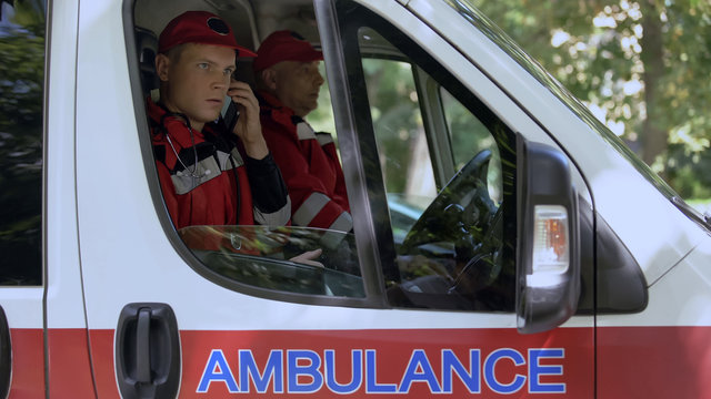 Male paramedic answering on patient call, professional ambulance crew, 911