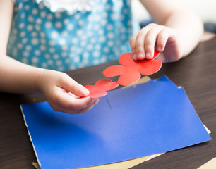 cute smiling baby 3 years old blonde-haired, blue-eyed shears out paper and sticks on paper