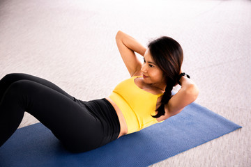 Close-up of young active and fitness Asian woman doing sit ups and crunches inside gym with exercise ball in background.