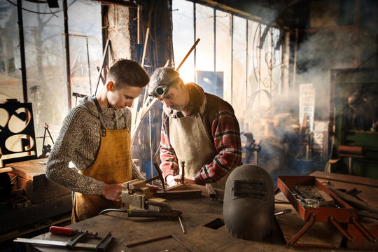 A craftsman in his workshop teaches his work to his apprentice