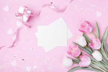 Women Day, Mother day background with envelope, gift box and beautiful spring tulip flowers on pastel pink desk. Flat lay.