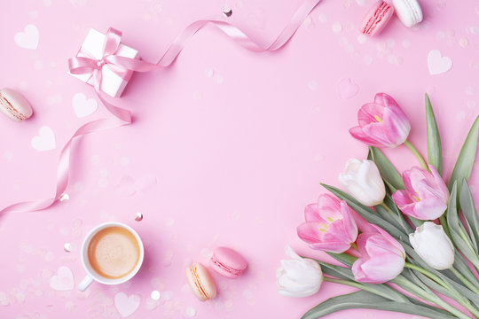 Morning cup of coffee, cake macaron, gift or present box and spring tulip flowers on pink background. Beautiful breakfast for Women day, Mother day. Flat lay.