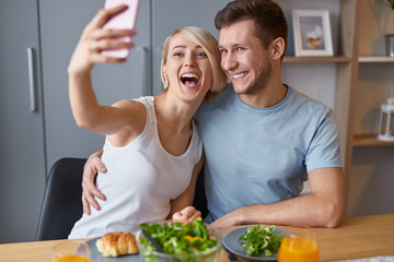 Playful girl with man taking selfie during breakfast