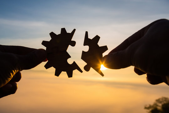 Silhouette Woman hands connecting couple puzzle piece against sunrise, Business solutions, target, success, goals and strategy concepts