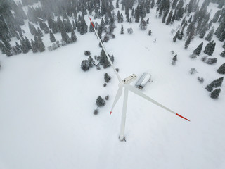 Aerial view of wind turbine in snow covered landscape in Swizterland. Tall pylon in fog, fir trees in the background.