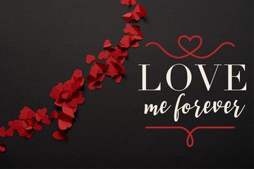 "top view of red small paper cut hearts on black background with ""love me forever"" lettering"
