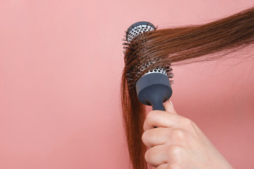 comb for hair volume in female hand on pink background