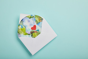 top view of envelope with planet picture on turquoise background, earth day concept