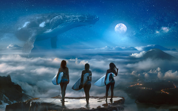 Surreal dream with three surfer girls standing on the top above clouds and landscape, big whale hovering in the space under full moon on background
