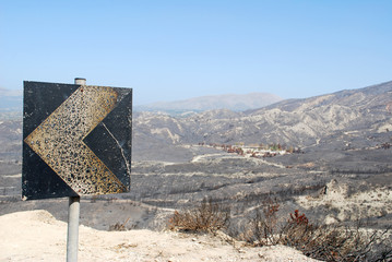 Burnt sign by the road and view of the mountain and valley after a fire, Rhodes Island, Greece