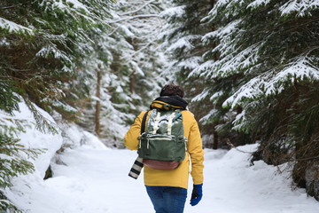 The photographer is walking in winter forest