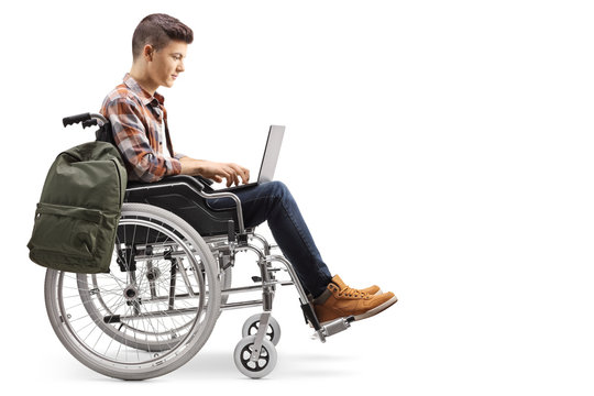 Disabled teenage male student working on a laptop in a wheelchair