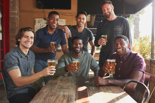 Group Of Male Friends Meeting In Sports Bar Making Toast Together At Camera