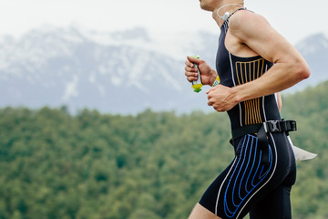 Fototapete - male athlete runner with energy gel in hand running on imountain marathon