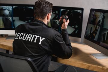 rear view of guard in uniform talking on walkie-talkie Wall mural
