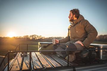 Junger Mann entspannt auf dem Dachgepäckträger seines Wohnmobils