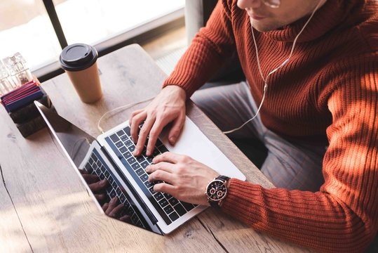 cropped view of man listening music in earphones and using laptop in cafe