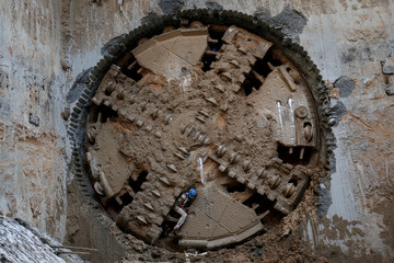 A construction worker comes through a Tunnel Boring Machine (TBM) breakthrough point after successfully building a tunnel for the metro train in Ahmedabad