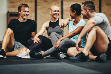 Smiling friends sitting in a gym after working out