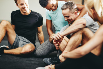 Laughing group of diverse friends sitting together in a gym