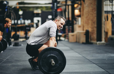 Smiling man preparing to lift weights at the gym