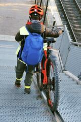 femme poussant son vélo sur une rampe d'escalier aménagée